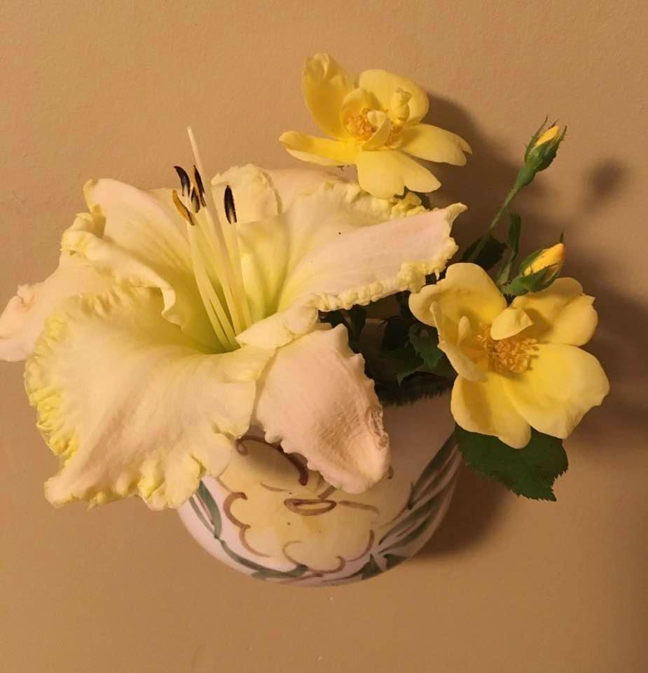vase with yellow daylily and roses